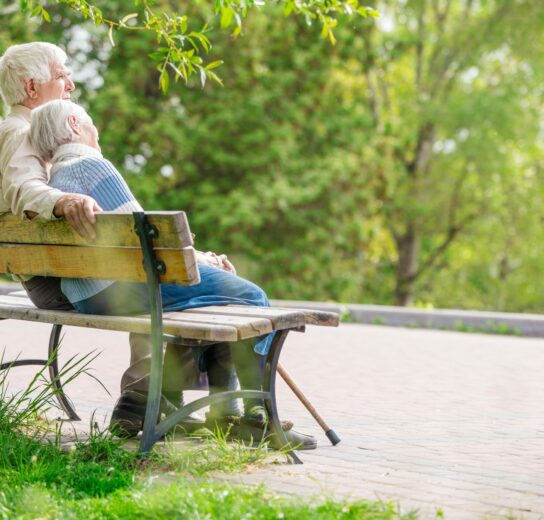 mature couple sitting on wood park bench