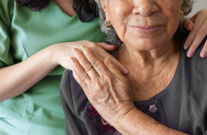 mature woman and caregiver touching hands