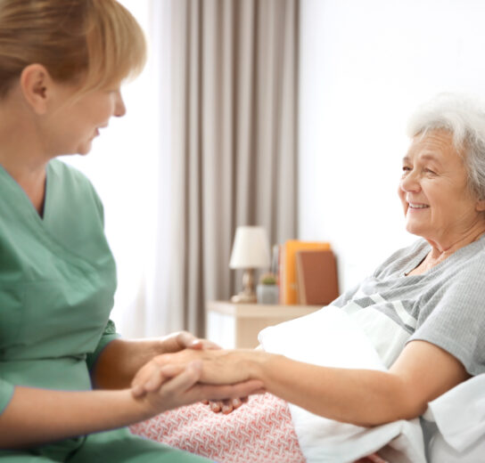 mature woman in bed offering her hand to professional female caregiver
