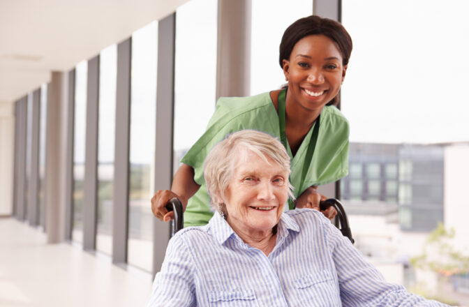 mature person in wheelchair being helped by professional caregiver