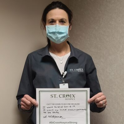 healthcare professional holding vaccine champion certificate