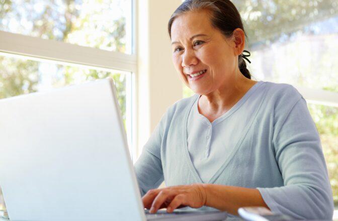 elderly woman typing on laptop
