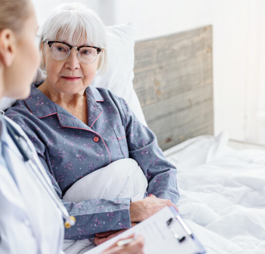 mature woman in bed listening to healthcare professional with clipboard