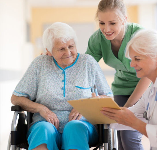 mature woman in wheelchair being assisted by a healthcare professional and listening to a second healthcare professional with clipboard and stethoscope