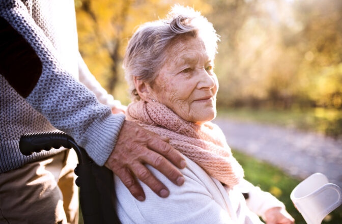 mature woman in wheelchair with mature man's hand on her shoulder