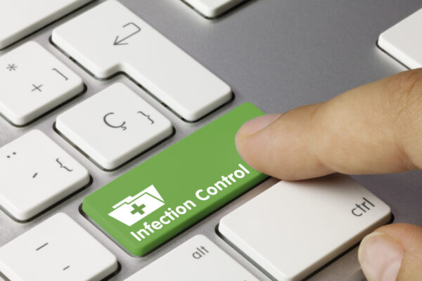 Index finger pressing green enter button labelled infection control on a keyboard