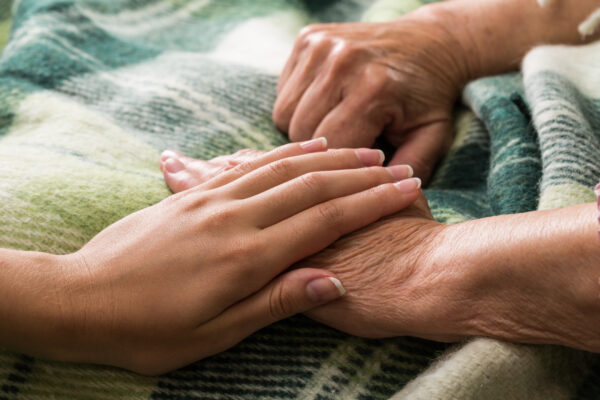 young woman's hand on top of elderly persons hand