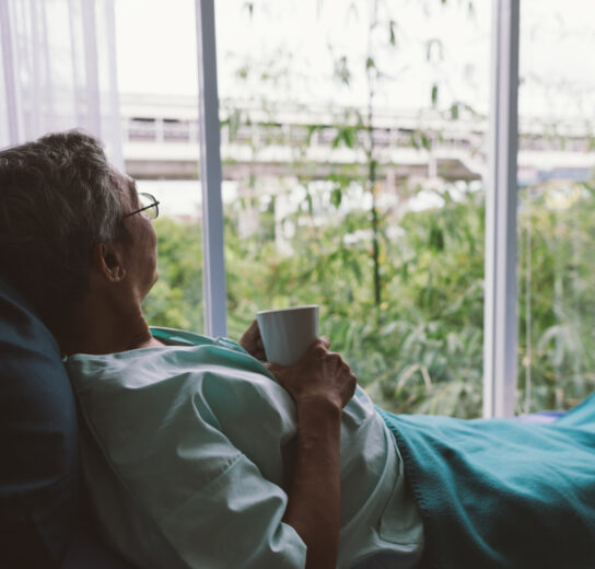 elderly person looking out window