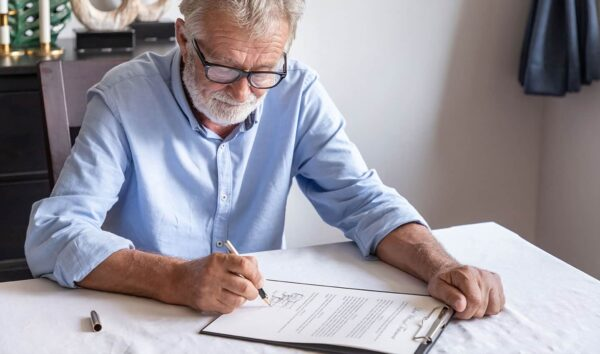 Mature man signing a contract