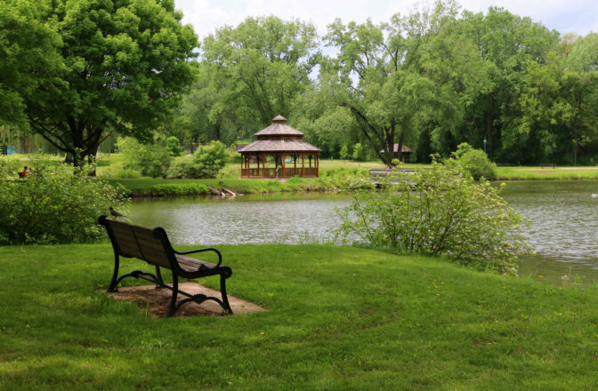 wood and metal bench in green surroundings near stream with gazebo across water