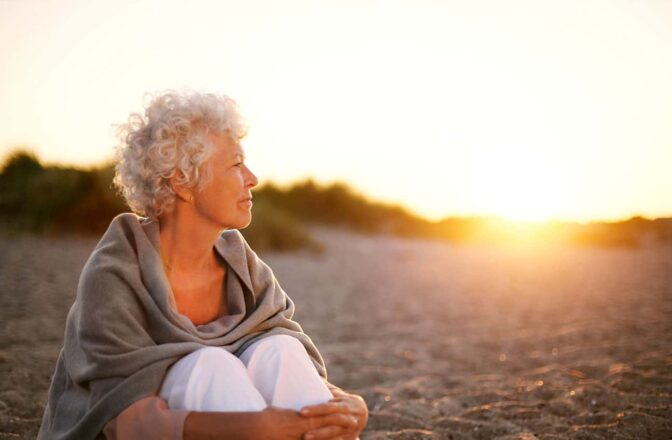 Mature woman sitting on a beach looking at a sunset