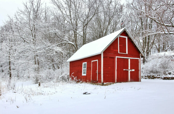 winter scene of small red barn and trees covered in snow