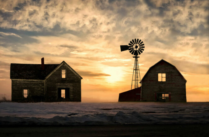 winter scene of house and barn with windmill at sunset
