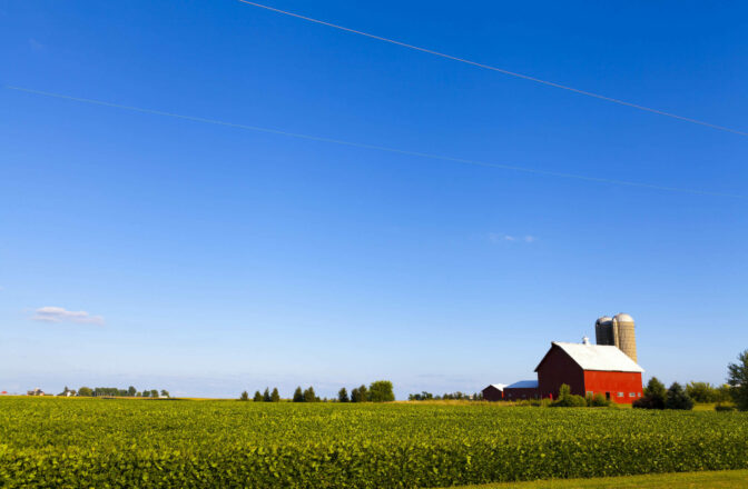 open blue sky and agriculture land with red bar and grain silos