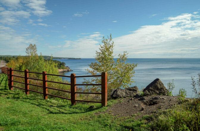 lakeshore view with wood and metal fence