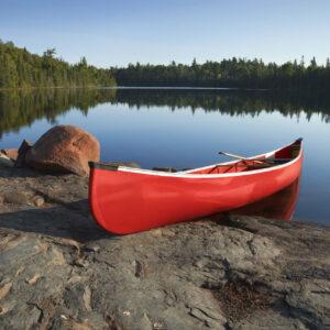 red plastic canoe resting on shore on still lake