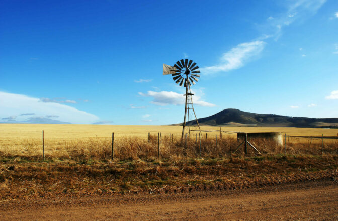 windmill near wire fence along dirt road with bluffs in the distance